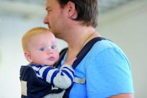 Un papa et son bébé dans un porte-bébé