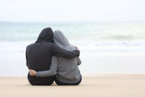 Un couple de dos s'enlace et contemple l'océan