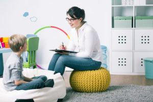 Une jeune femme est assise face à un enfant et prend des notes