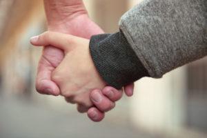 Une main d'adulte tient une main d'enfant
